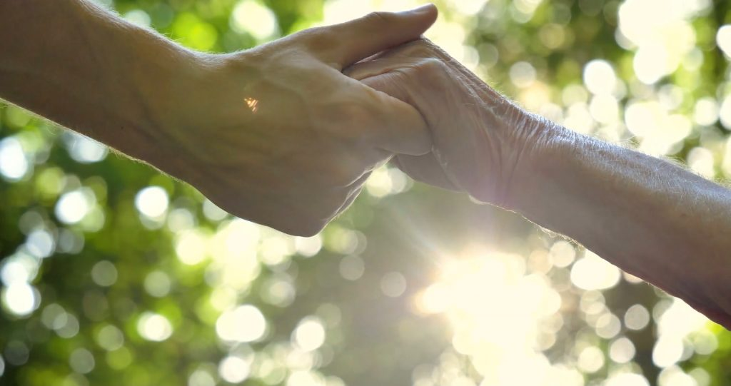 Hands holding with sunlight behind